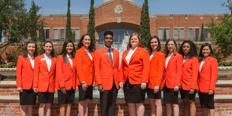 The Student Foundation members pictured together in a row, wearing matching orange blazers.