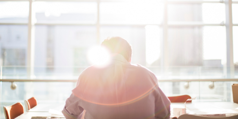 Man studying at a desk with sunlight coming through the windows