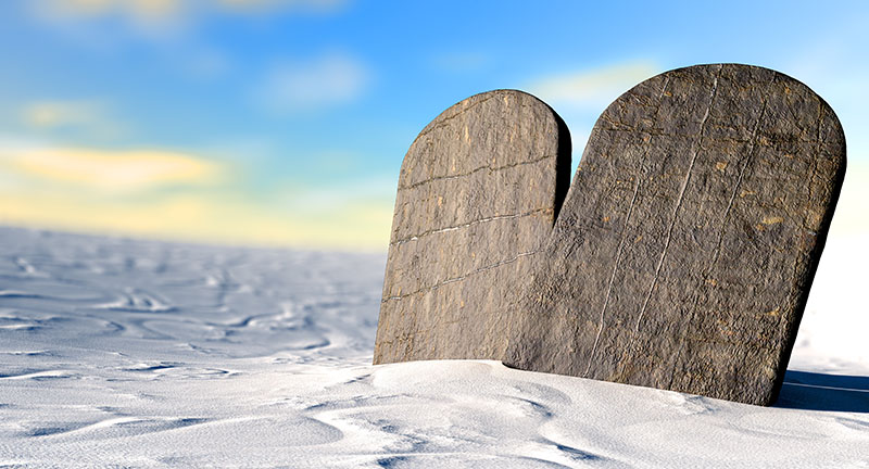 Two stone tablets representing the ten commandments standing in brown desert sand infront of a blue sky